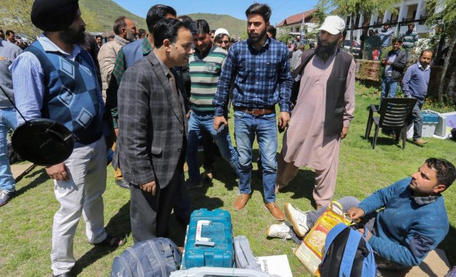 Election officials collect EVMs and and other material for the first phase of Lok Sabha elections, at a distribution centre in Barmamulla district of north Kashmir, April, 10, 2019. (PTI Photo)