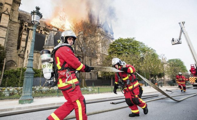 This photo provided Tuesday April 16, 2019 by the Paris Fire Brigade shows fire fighters pulling a hose by the burning Notre Dame cathedral, Monday April 15, 2019. Experts assessed the blackened shell of Paris\' iconic Notre Dame Tuesday morning to establish next steps to save what remains after a devastating fire destroyed much of the cathedral that had survived almost 900 years of history. AP/PTI