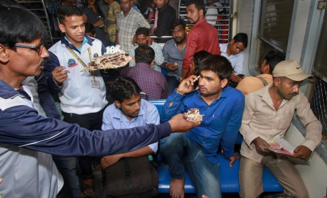 Railway employees offer cake to commuters as they commemorate the 166th year of Indian Railways, in Thane, Tuesday, April 16, 2019. On April 16, 1853, the first passenger train of Indian Railways ran between Bori Bunder (Mumbai CSMT) and Thane. PTI