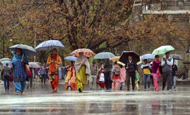 Pedestrians carry umbrellas during rain, in Shimla, Tuesday, April 16, 2019. PTI