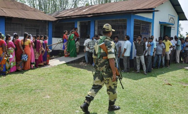 Siliguri: A security personnel stands guard as voters queue to cast their vote during the second phase of general elections, at a polling station, in Siliguri, Thursday, April 18, 2019. PTI
