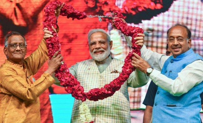 Prime Minister Narendra Modi being garlanded at \'Traders Sammelan\' at Talkatora Stadium, in New Delhi, Friday, April 19, 2019. (PTI Photo/Kamal Kishore)