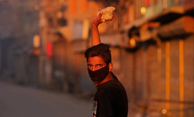 A masked Kashmiri demonstrator looks on as he prepares to throw a stone towards Indian police during a protest after the end of the second phase of general election in Srinagar April 18, 2019. REUTERS/Danish Ismail