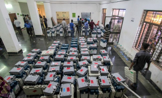 Election staff inspect the boxes containing EVMs and other election material ahead of the third phase of the 2019 Lok Sabha elections, at a distribution centre, in Bhubaneswar, Sunday, April 21, 2019. (PTI Photo)