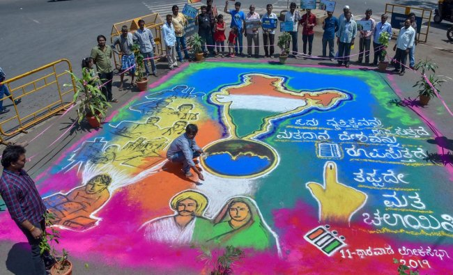 Visitors gather around a \'Rangoli\' painted to create awareness among the voters ahead of the Lok Sabha elections, in Hubli, Sunday, April 21, 2019. (PTI Photo)