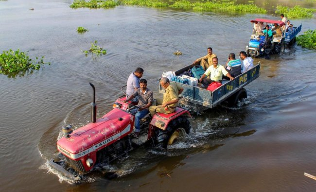 Election officials along with security personnel travel by tractors to reach a polling station, at Hajo in Kamrup district of Assam, Monday, Apr 22, 2019. (PTI Photo)