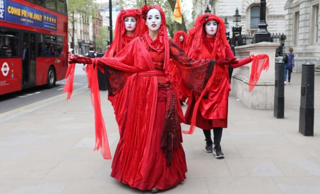 Extinction Rebellion climate change activists in red costume walk along Whitehall in Westminster, London on April 23, 2019. (Photo by ISABEL INFANTES / AFP)