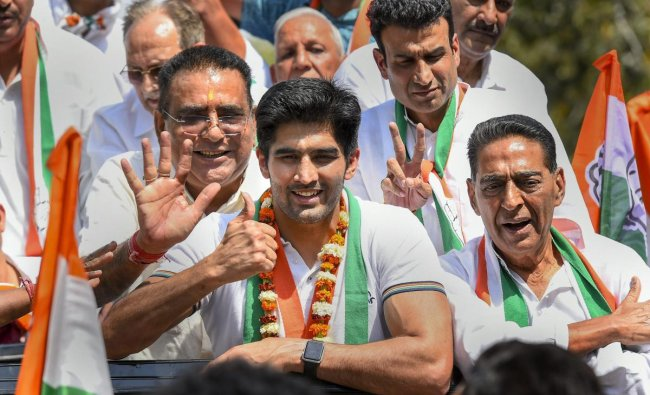 Boxer and Congress candidate from South Delhi constituency Vijender Singh flashes the victory sign during his nomination filing procession for the Lok Sabha polls, in New Delhi, Tuesday, April 23, 2019. (PTI Photo/Kamal Singh)
