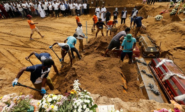 Coffins are laid in the ground during a mass burial for victims at a cemetery near St Sebastian\'s Church in Negombo, three days after a string of suicide bomb attacks on churches and luxury hotels across the island on Easter Sunday, in Sri Lanka April 24, 2019. REUTERS/Thomas Peter