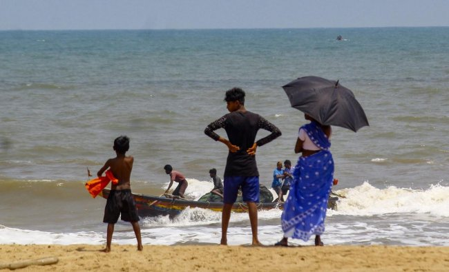 Fishermen return to anchor their boat after they were advised not to venture into the sea in the view of cyclonic storm 'Fani', at Puri beach. (PTI Photo)