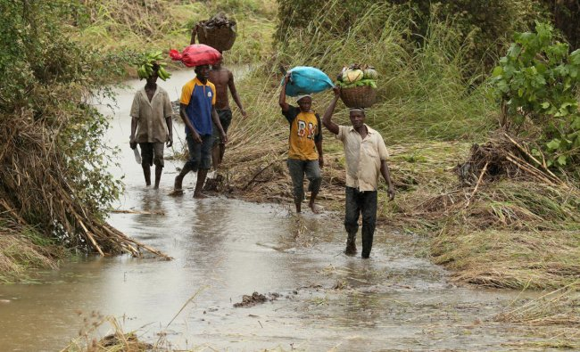 Villagers carry goods through the fields flooded in the aftermath of Cyclone Kenneth, along the Mieze river near Pemba, Mozambique. (AP/PTI Photo)