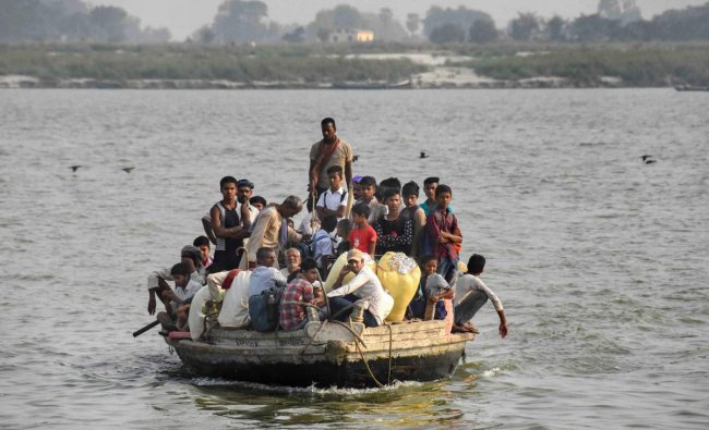 An overcrowded boat ferries passengers across river Ganga, in Patna. (PTI Photo)