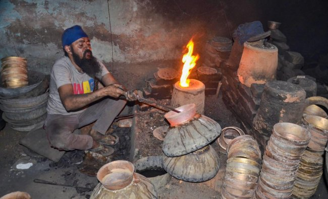 A worker moulds brass to make a utensil on International Labour Day, at a workshop in Mirzapur, Uttar Pradesh. (PTI Photo)