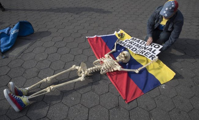 A supporter of Venezuelan opposition leader Juan Guaido secures a skeleton to a Venezuelan flag during a rally in New York\'s Union Square. (AP/PTI Photo)