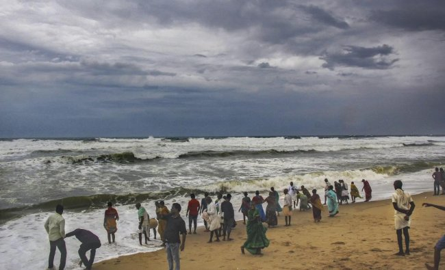 Villagers at the beach as dark clouds hover above the sea ahead of cyclone \'Fani\', in Puri. (PTI Photo)
