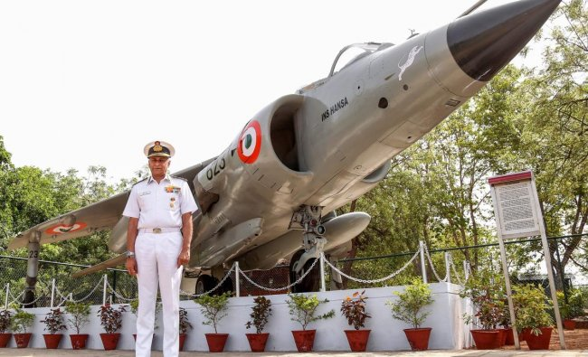 Indian Navy chief Admiral Sunil Lanba poses for photographs near the Sea-Harrier fighter aircraft at the Mayo College in Ajmer, Rajasthan. (PTI Photo)