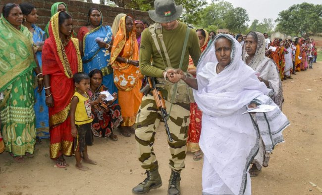 A paramilitary jawan helps an aged woman at a polling booth during the sixth phase of Lok Sabha elections, in Purulia district of West Bengal, Sunday, May 12, 2019. (PTI Photo)