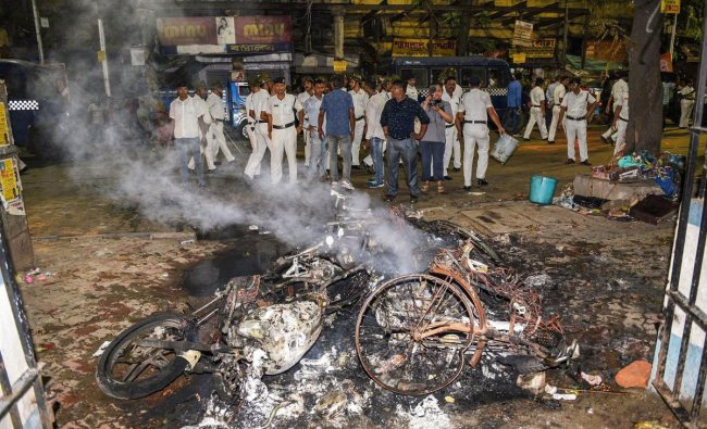 Police personnel look on near vehicles burnt by a mob during BJP President Amit Shah\'s election roadshow for the last phase of Lok Sabha polls, in Kolkata, Tuesday, May 14, 2019. (PTI Photo)