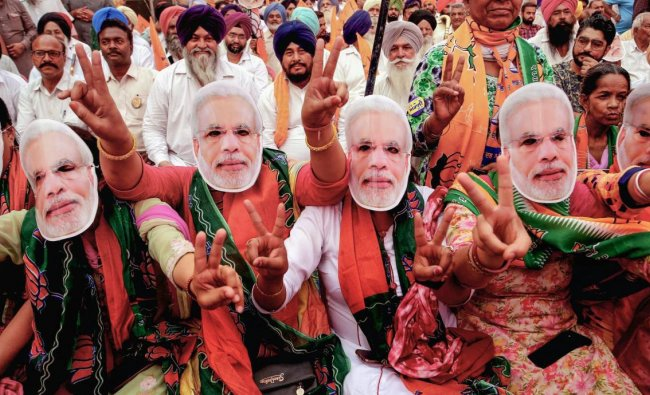 BJP supporters wear masks of Prime Minister Narendra Modi during an election rally for the last phase of the Lok Sabha polls, in Patiala, Thursday, May 16, 2019. (PTI Photo)
