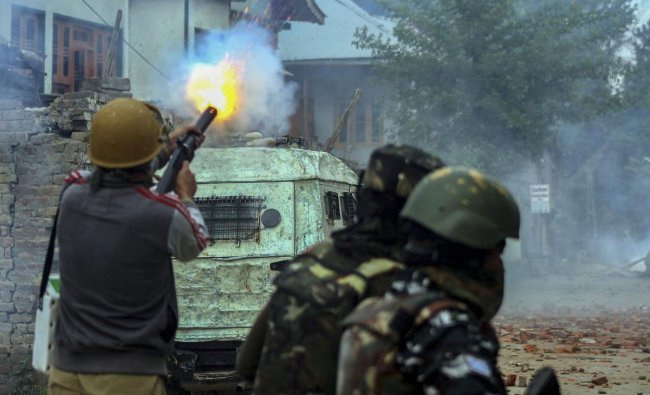 Policemen fire tear gas at protestors near the encounter site in which three top Jaish-e-Muhammad militant commanders, one army soldier and a civilian were killed, in Pulwama district, Thursday, May 16, 2019. (PTI Photo)