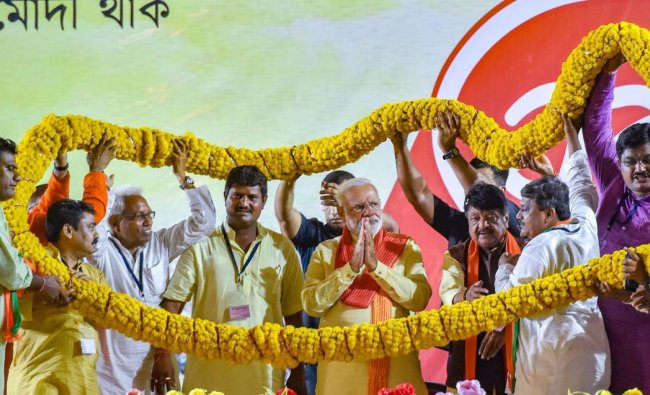 Prime Minister Narendra Modi being garlanded during an election campaign rally for the ongoing Lok Sabha polls, in Kolkata , Thursday, May 16, 2019. (PTI Photo)