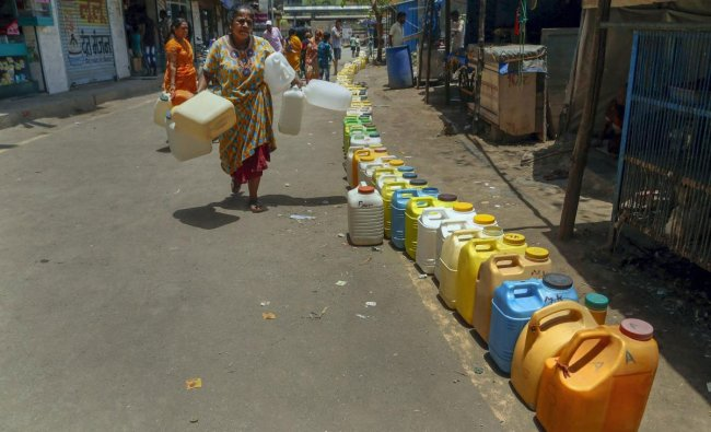 A woman walks along a long queue of plastic containers to collect water on a hot summer day, at Diva residential area in Thane, Thursday, May 16, 2019. (PTI Photo)