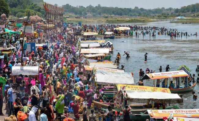 People gather at Gwarighat on the banks of river Narmada to take bath, on the occasion of Somvati Amavasya in Jabalpur. (PTI Photo)