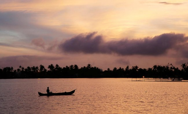 A man rows his boat in the tributary waters of Vembanad Lake against the backdrop of pre-monsoon clouds on the outskirts of Kochi, India, June 7, 2019. REUTERS/Sivaram