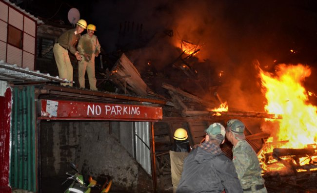Firefighters douse a blaze which broke out in an old building, in Lakkar Market, Shimla, Thursday, June 6, 2019. (PTI Photo)