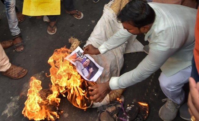 BJP workers burn a photograph of Chief Minister Mamata Banerjee during a protest against alleged failure of law and order situation, and killing of the party workers in the various districts of West Bengal, in Kolkata, Sunday, June 9, 2019. (PTI Photo/Ashok Bhaumik)