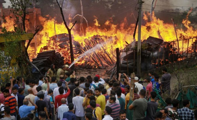 People watch as firefighters douse flames at a timber godown, in Toph Sherkhanian area of Jammu, Tuesday, June 11, 2019. (PTI Photo)
