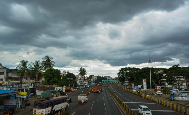Vehicles ply on road as dark clouds hover in the sky, on Pune-Bangalore Nationl Highway, in Karad, Tuesday, June 11, 2019. (PTI Photo)