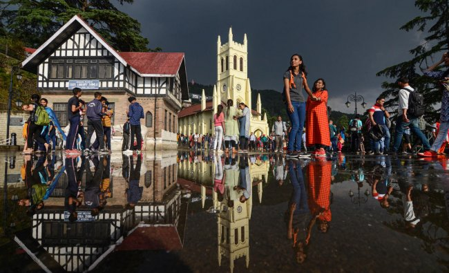 Tourists move out to the open after a rain shower as weather turned pleasant in the hill-station of Shimla, Tuesday, June 11, 2019. (PTI Photo)