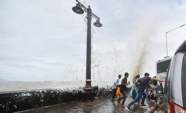 People react as a wave during high tide hits the seawall at Gateway of India, in Mumbai, Wednesday, June 12, 2019. (PTI Photo/Mitesh Bhuvad)