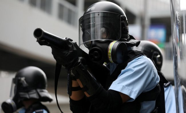 Police officer aims a tear gas gun at protesters during a demonstration against a proposed extradition bill in Hong Kong, China June 12, 2019. REUTERS/Athit Perawongmetha