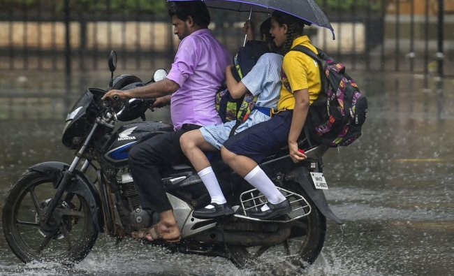 Students share an umbrella on a bike during heavy rainfall in Mumbai, Tuesday, June 18, 2019. PTI
