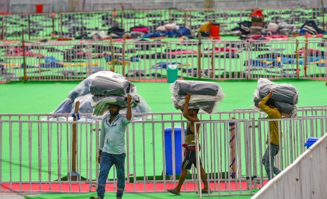 Workers carry yoga mats in preparation at the venue of 5th International Yoga Day, in Ranchi, Thursday, June 20, 2019. Prime Minister Narendra Modi will be joining the programme in the city on Friday. PTI