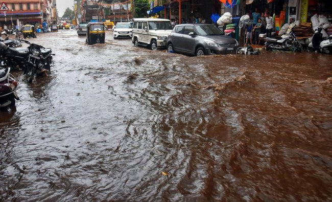 People wade through a waterlogged road after rains in Hubbali, Sunday, June 23, 2019. (PTI Photo)