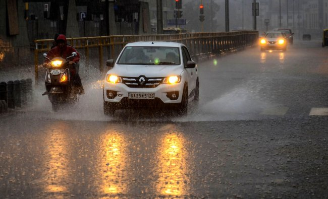 Vehicles move with their headlights on during rains in Hubbali, Sunday, June 23, 2019. (PTI Photo)
