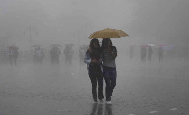 Pedestrian protect themselves with an umbrella during a downpour in the hill-station of Shimla, Monday, June 24, 2019. (PTI Photo)