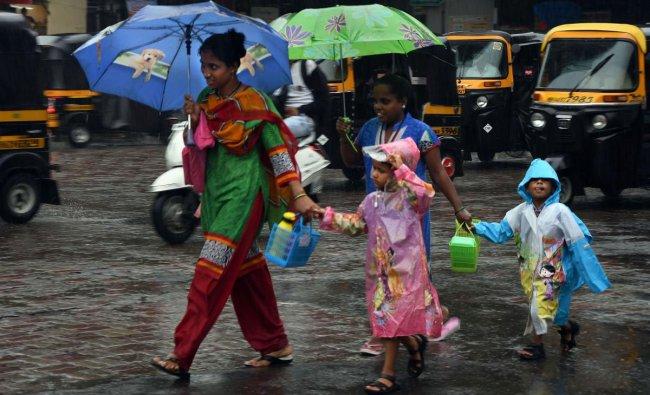 Pedestrians walk across a road during monsoon rain, in Thane, Monday, June 24, 2019. (PTI Photo)