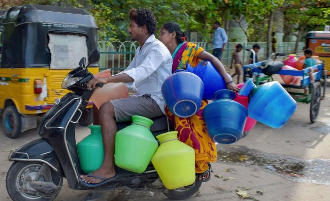 A couple rides on a scooter carrying empty vessels to fetch water from a municipal water tanker, following acute water shortage, in Chennai, Wednesday, June 26, 2019. (PTI Photo)