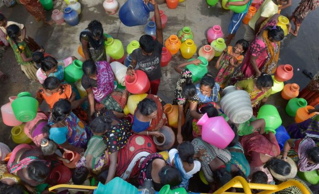 People rush to fill their vessels from a water tanker following acute water shortage, in Chennai, Wednesday, June 26, 2019. (PTI Photo)