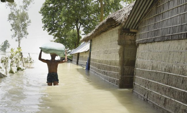 A man carries his belongings from a flood affected area to a safer place, in Morigaon district, Assam. (PTI Photo)