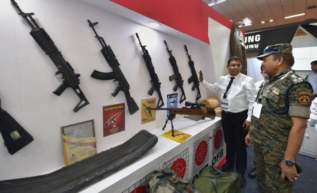 An exhibitor explains the features of a weapon to a visitor at the International Police Expo 2019, in New Delhi. (PTI Photo)