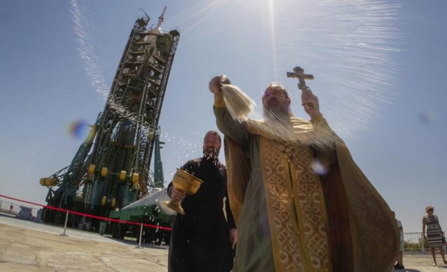 An Orthodox priest conducts a blessing service in front of the Soyuz FG rocket at the Russian leased Baikonur cosmodrome, Kazakhstan. (AP/PTI Photo)