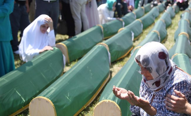 A Bosnian Muslim woman prays next to coffins during a mass funeral in the village of Kamicani, near Prijedor, Bosnia and Herzegovina. (Reuters Photo)