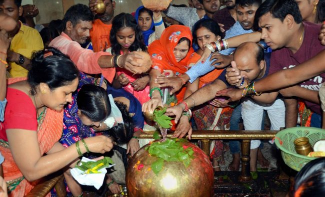Devotees perform \'Abhishek\' of Lord Shiva on the first Somwar (Monday) of the holy month of Shravan, at Pahari temple in Ranchi. (PTI Photo)