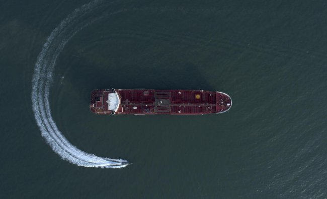An aerial view shows a speedboat of Iran\'s Revolutionary Guard moving around the British-flagged oil tanker Stena Impero which was seized in the Strait of Hormuz on Friday by the Guard, in the Iranian port of Bandar Abbas. (AP/PTI Photo)