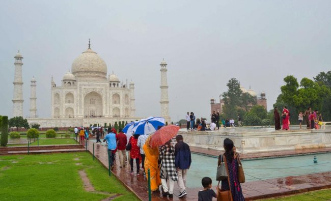Tourists visit the Taj Mahal on a rainy day, in Agra. (PTI Photo)
